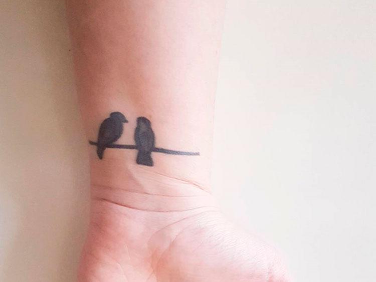 Два черных силуэта птиц на запястье