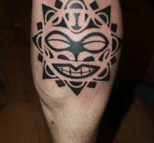 Черная полинезийская тату у мужчины на ноге