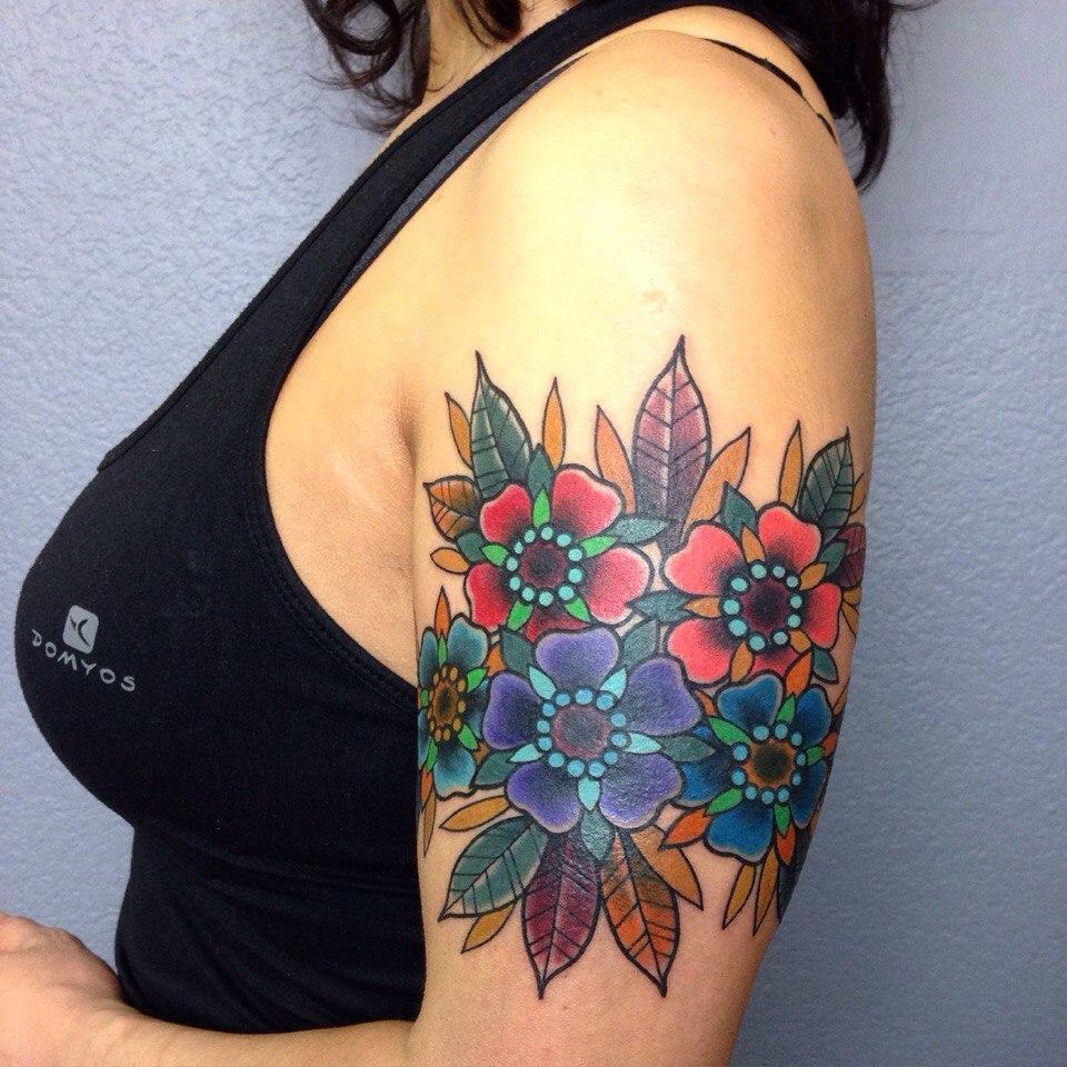 Красные и синие цветы у девушки на плече
