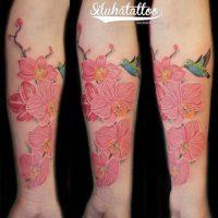 Розовые цветы и колибри на предплечье