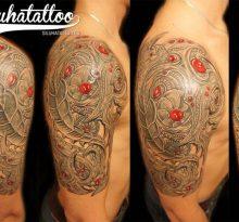 Серая тату с красными пятнами в стиле биомеханика на плече