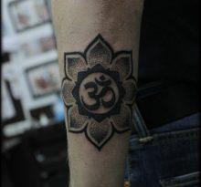 Символ Ом внутри цветка на предплечье