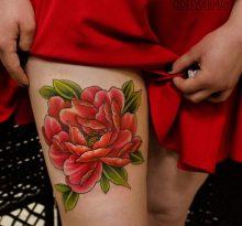 Красный цветок с зелеными листьями на бедре