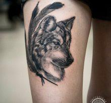 Тату волка с перьями на бедре