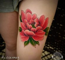Татуировка розового цветка на бедре