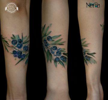 Синие ягоды и зеленые листки на предплечье