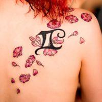 Знак Близнецов и маленькие цветы на спине у девушки