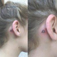 Символ Весов у девушки за ухом