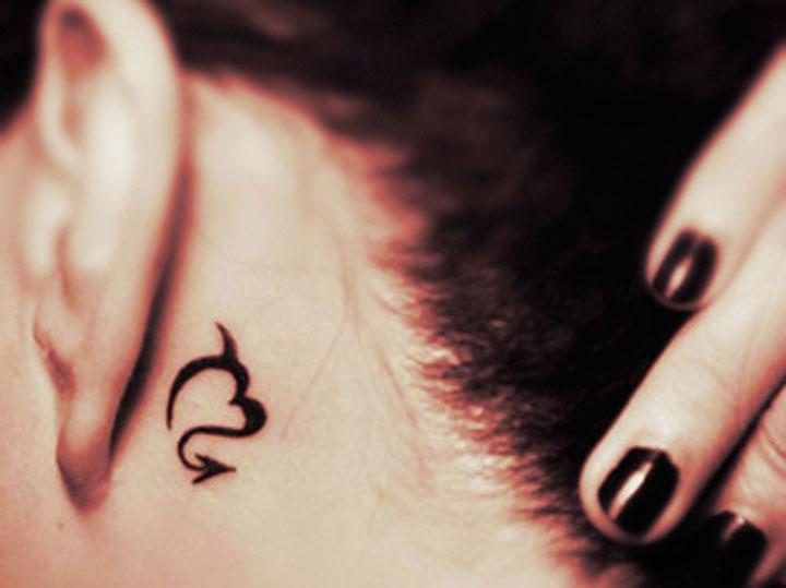Знак Скорпиона за ухом у девушки