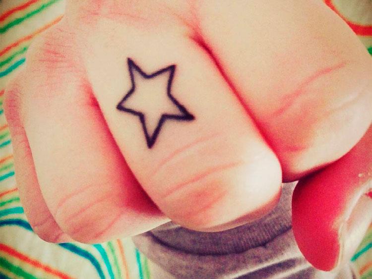 Маленькая черная тату звезды на пальце