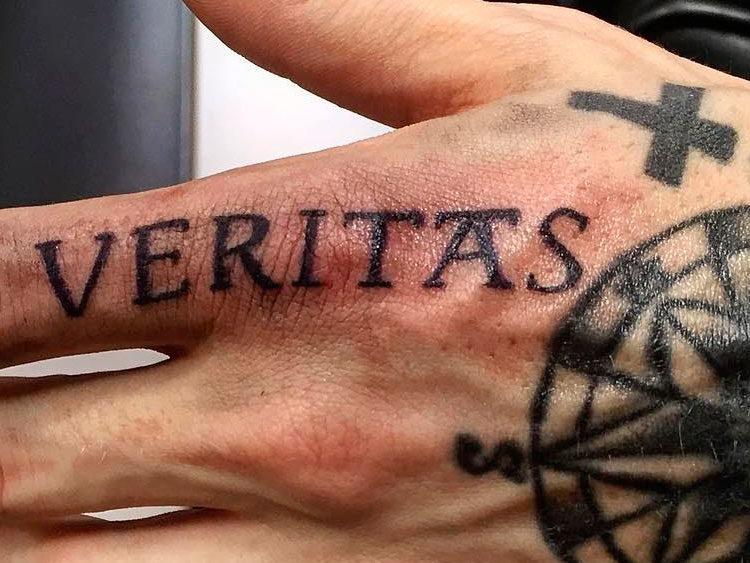 Надпись Veritas и компас на руке