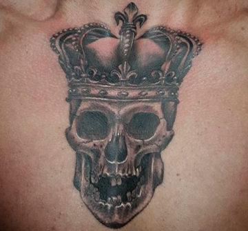 Череп с короной на груди у мужчины