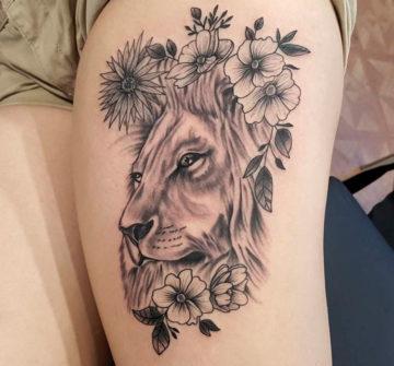 Голова льва с цветами на бедре у девушки