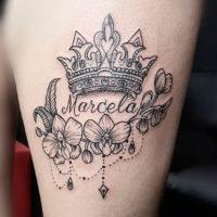 Корона, имя и цветы на бедре у девушки