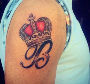 Корона с буквой на плече у мужчины
