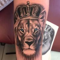 Лев с короной на предплечье у девушки
