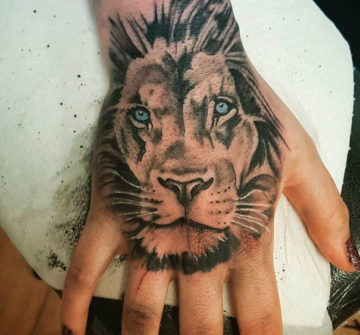 Тату льва на кисти руки у девушки