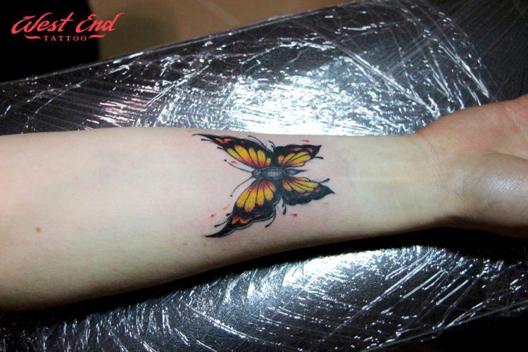 Черно-желтая бабочка на руке