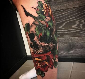 Череп с розой и зелеными листьями, тату на ноге
