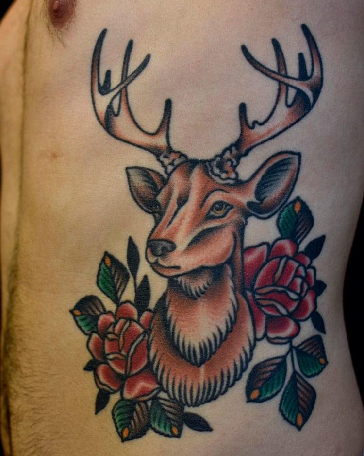 Тату олень с розами на боку у мужчины