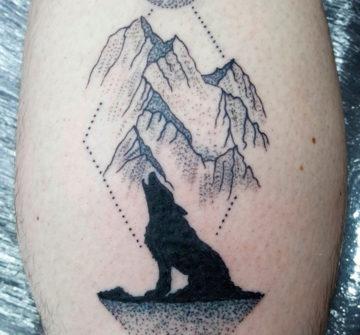 Воющий волк на фоне гор