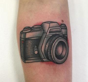 Фотоаппарат, тату на предплечье у девушки