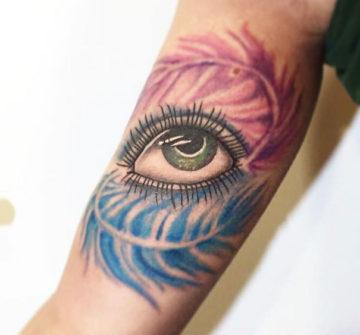 Глаз с перьями, женская тату на бицепсе