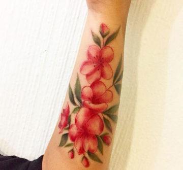 Розовые цветы с листьями, тату на руке у девушки