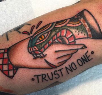 Змея кусающая руку, традиционная тату на предплечье
