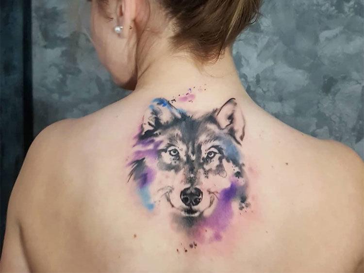 Голова волка в стиле акварель, тату на спине у девушки