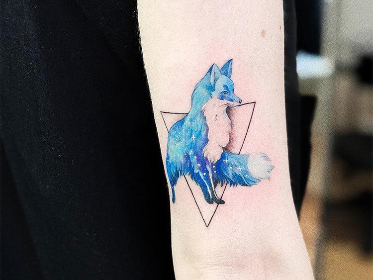 Синяя лиса в треугольнике, тату на руке у девушки