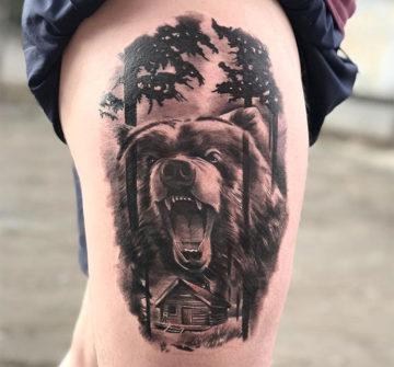 Ревущий бурый медведь, деревья и избушка, мужская тату на бедре