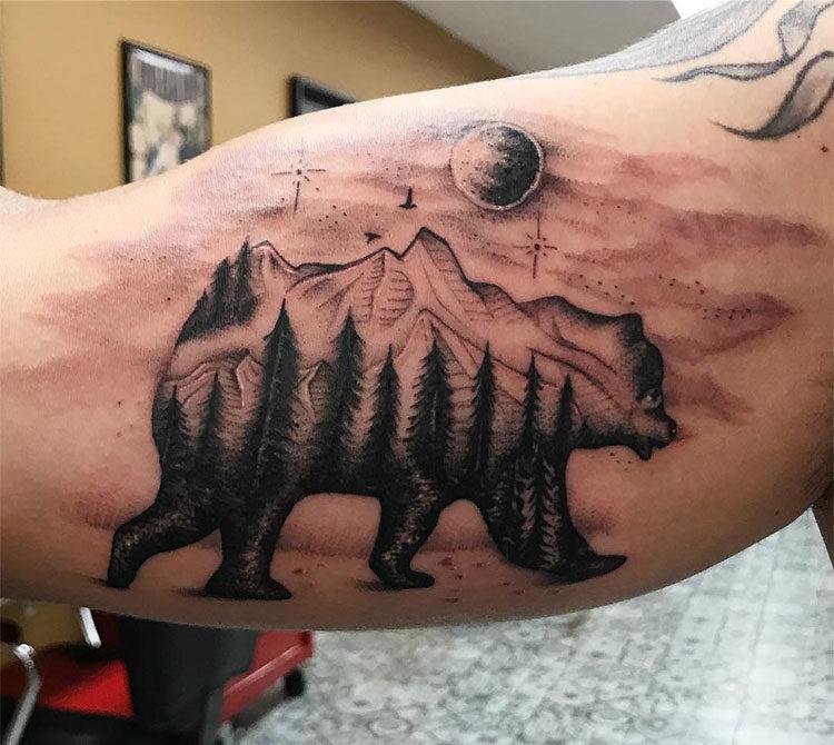 Силуэт медведя с деревьями и горами, мужская тату на бицепсе